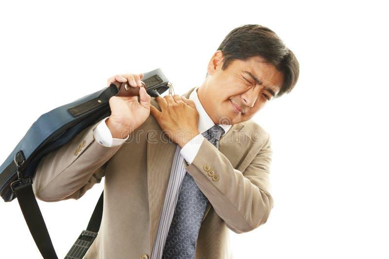 Geschäftsmann mit den Schulterschmerz. lizenzfreie stockfotos
