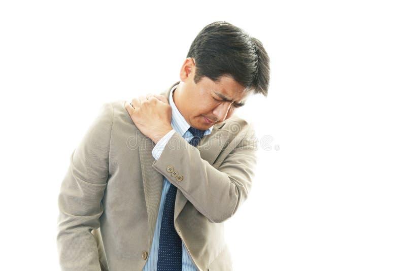 Geschäftsmann mit den Schulterschmerz. stockfotos