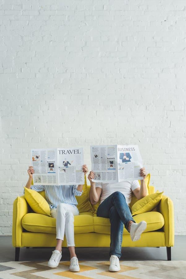 Geschäftsmann mit der Freundin, die auf Sofa sitzt und Zeitungen über Reise und Geschäft liest lizenzfreie stockbilder