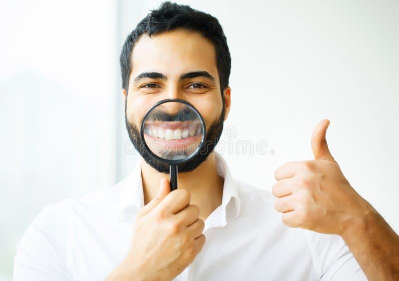 Geschäftsmann mit der Lupe, die auf sein Lächeln laut summt lizenzfreies stockbild