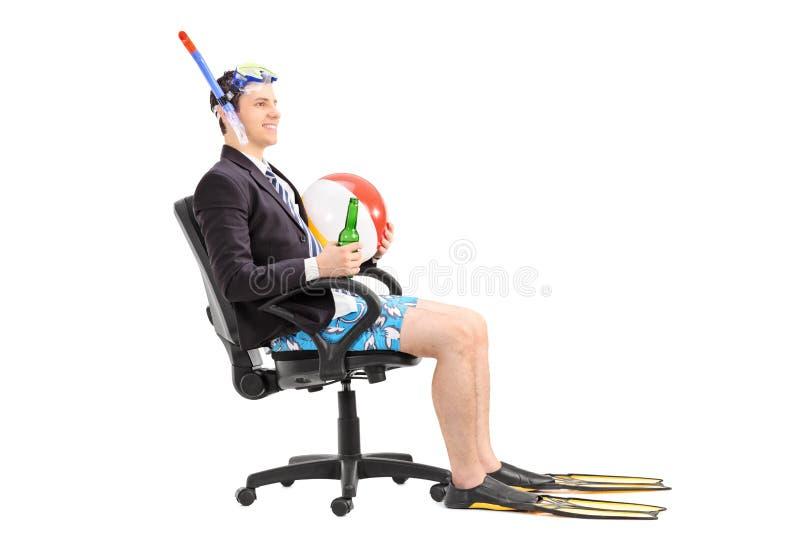 Geschäftsmann mit der Schnorchel, die in einem Bürostuhl sitzt lizenzfreies stockbild