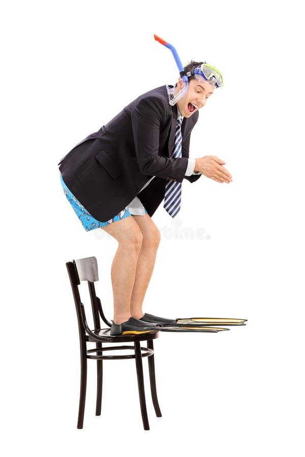 Geschäftsmann mit der Schnorchel, die weg von einem Stuhl springt lizenzfreie stockfotos