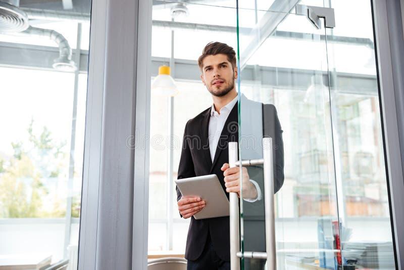 Geschäftsmann mit der Tablette, welche die Tür in Büro anmeldet stockbild