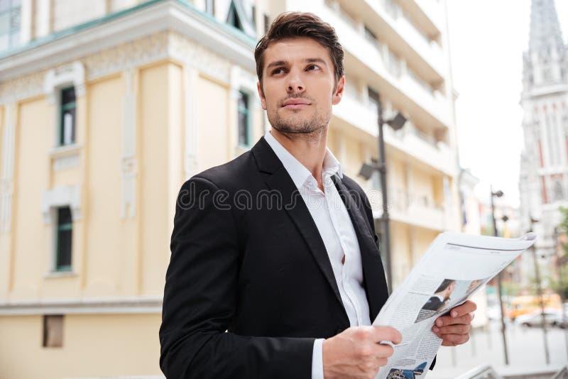 Geschäftsmann mit der Zeitung, die auf der Straße steht lizenzfreie stockfotografie