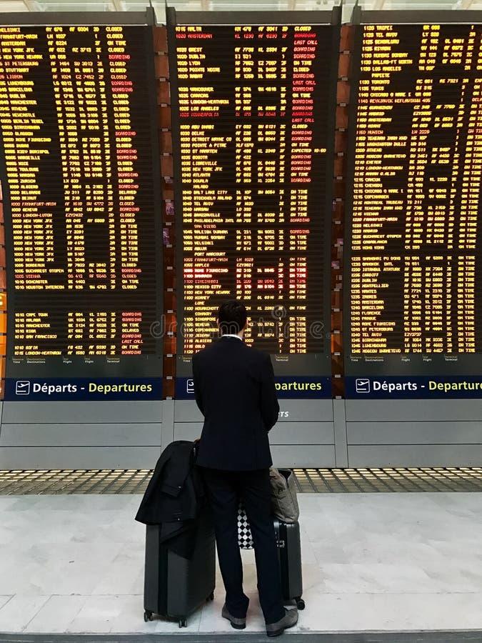 Geschäftsmann mit einem Aktenkoffer auf einem Hintergrund des Abfahrtbrettes am Flughafen lizenzfreie stockfotografie