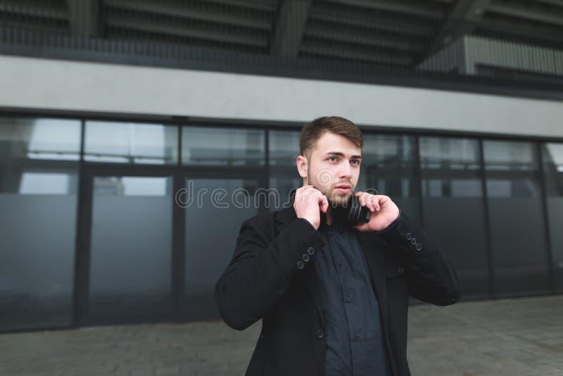 Geschäftsmann mit einem Bart und Kopfhörern auf dem Hals wirft vor dem hintergrund der Wände eines modernen Gebäudes auf lizenzfreies stockfoto