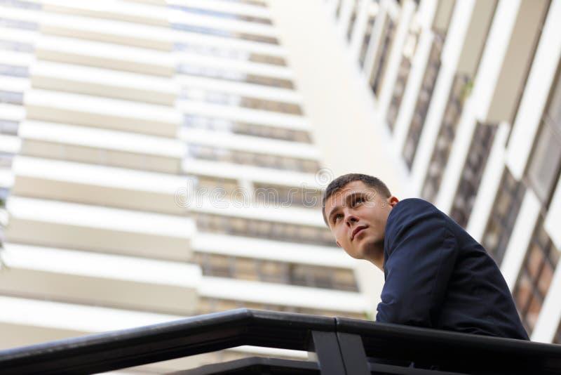 Geschäftsmann mit einem Gebäude im Hintergrund stockfotografie