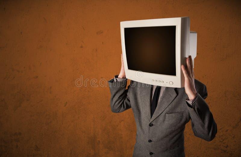 Geschäftsmann mit einem Monitor auf seinem Kopf und braunen leeren Raum lizenzfreie stockfotografie
