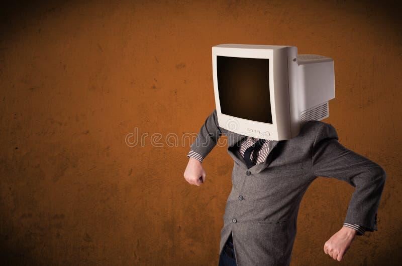 Geschäftsmann mit einem Monitor auf seinem Kopf und braunen leeren Raum lizenzfreies stockbild