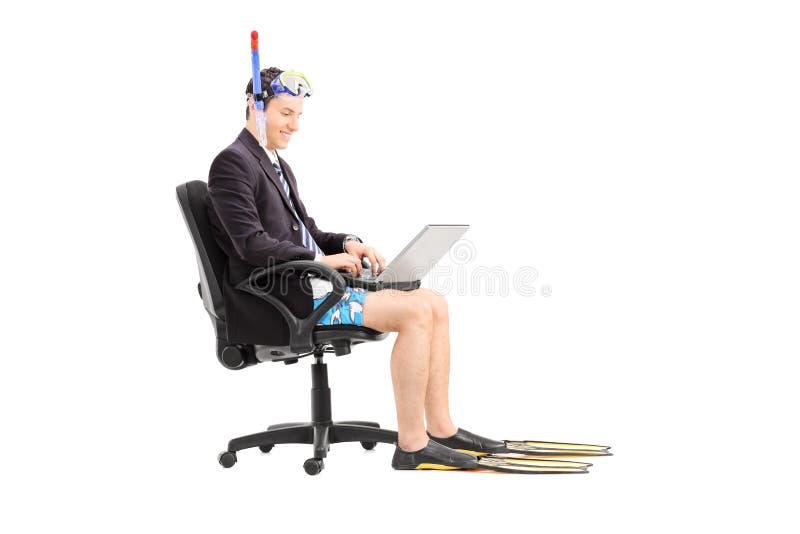 Geschäftsmann mit einer Schnorchel, die an Laptop arbeitet stockbild