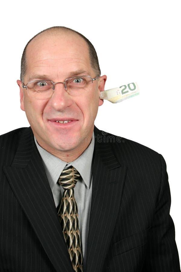Geschäftsmann mit Geld aus seinem Ohr heraus lizenzfreie stockfotos