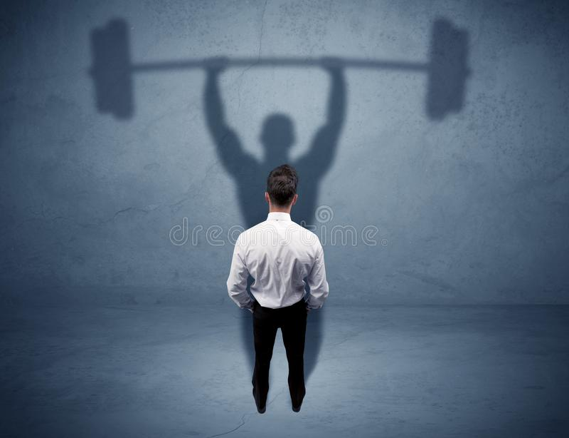Geschäftsmann mit Gewichthebenschatten lizenzfreies stockfoto