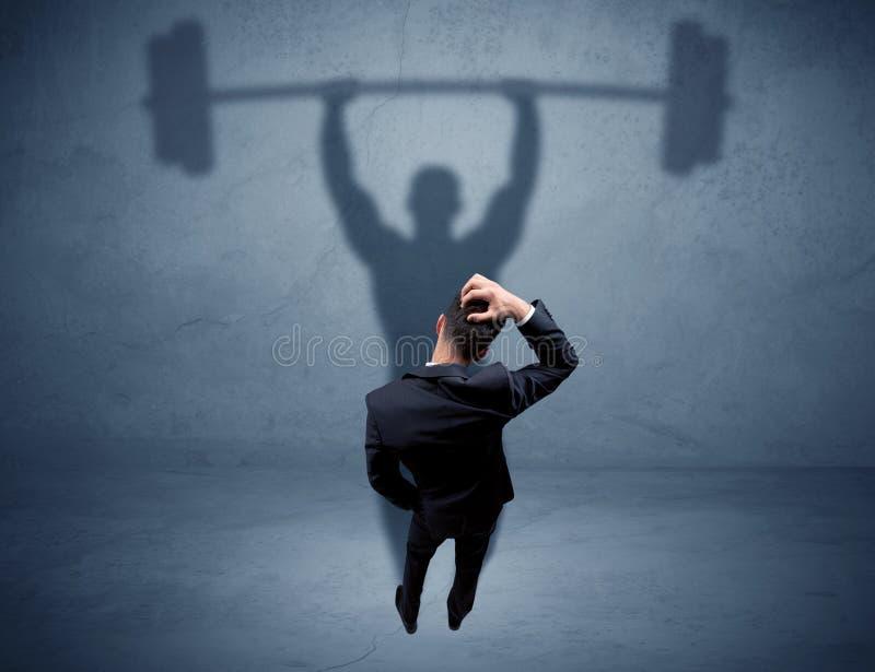 Geschäftsmann mit Gewichthebenschatten stockfoto