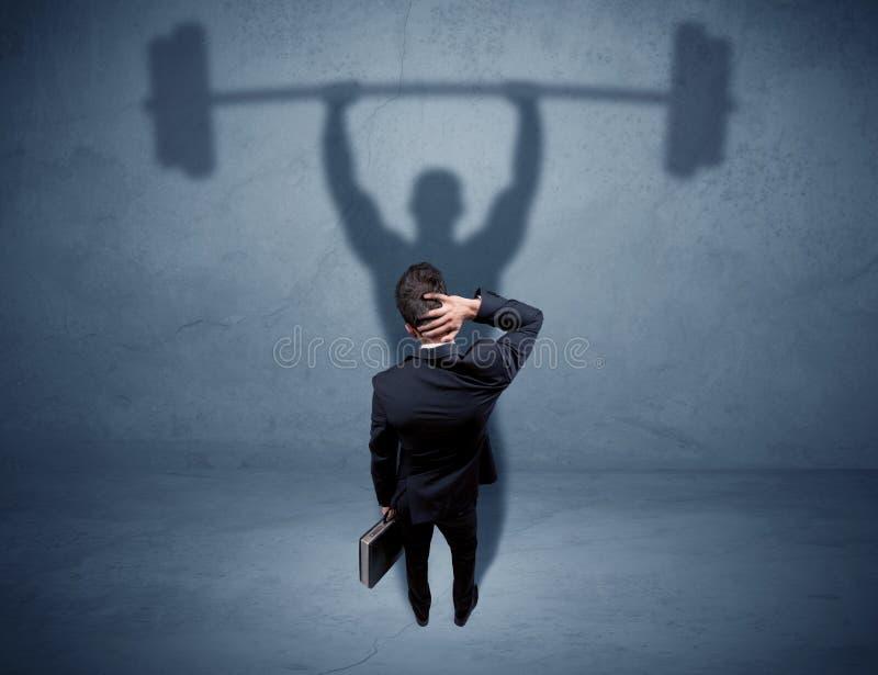 Geschäftsmann mit Gewichthebenschatten lizenzfreie stockfotografie
