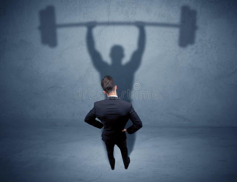 Geschäftsmann mit Gewichthebenschatten lizenzfreies stockbild