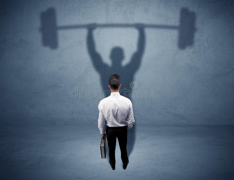Geschäftsmann mit Gewichthebenschatten stockbild