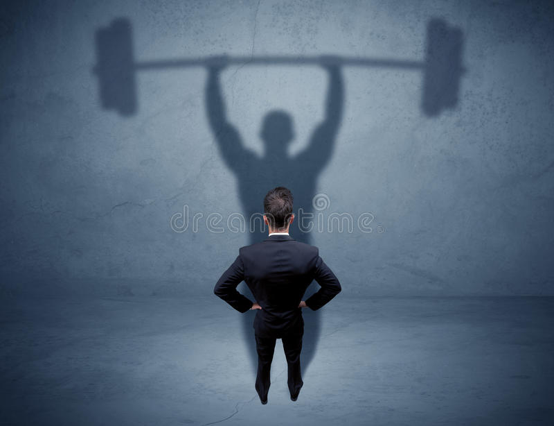 Geschäftsmann mit Gewichthebenschatten stockfotografie