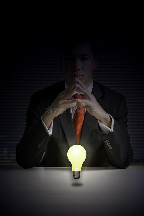 Geschäftsmann mit glühender Glühlampe stockfoto