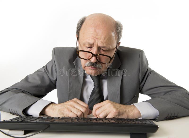 Geschäftsmann mit Kahlkopf auf seiner Funktion 60s betont und frustriert am Bürocomputer-Laptopschreibtisch, der müde schaut lizenzfreie stockfotografie