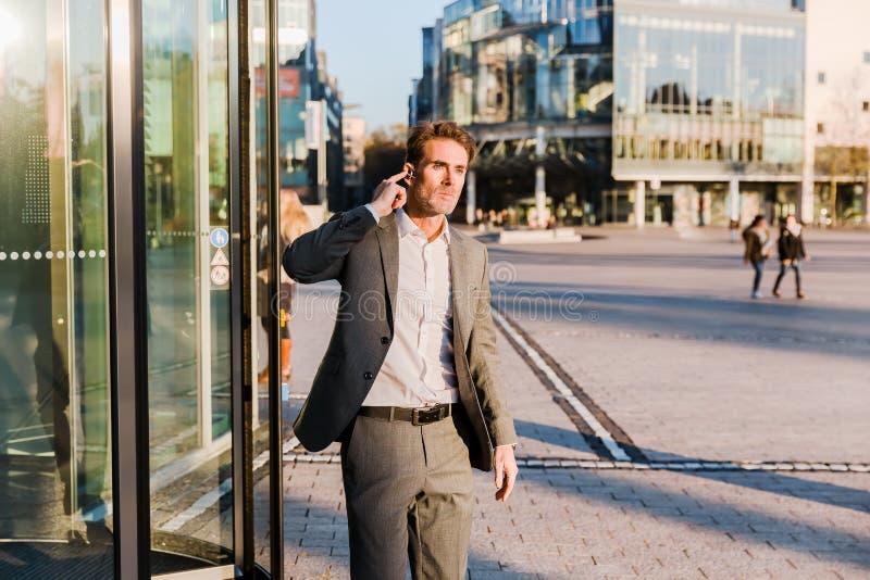 Geschäftsmann mit Kopfhörern kommt aus ein Bürogebäude heraus stockbild