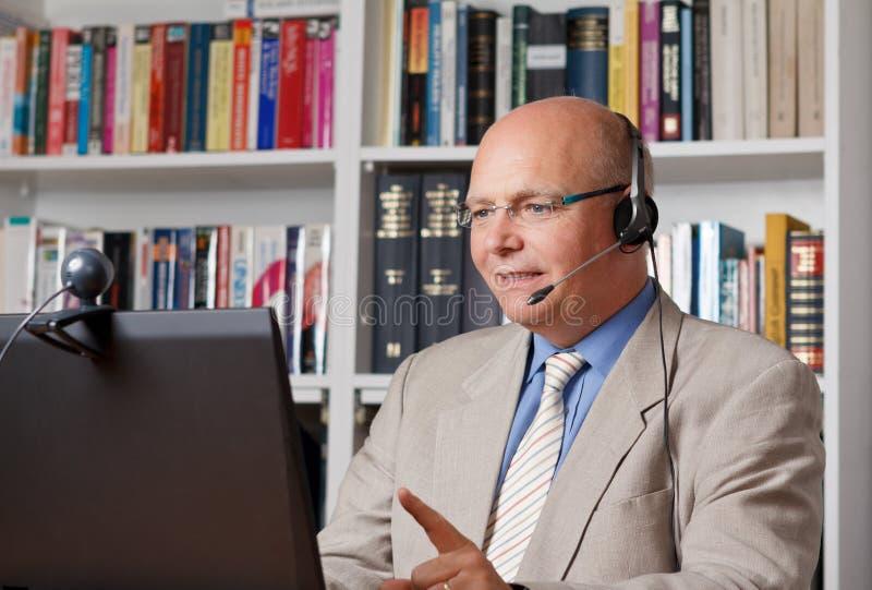 Geschäftsmann mit Kopfhörern und Webcam lizenzfreie stockbilder