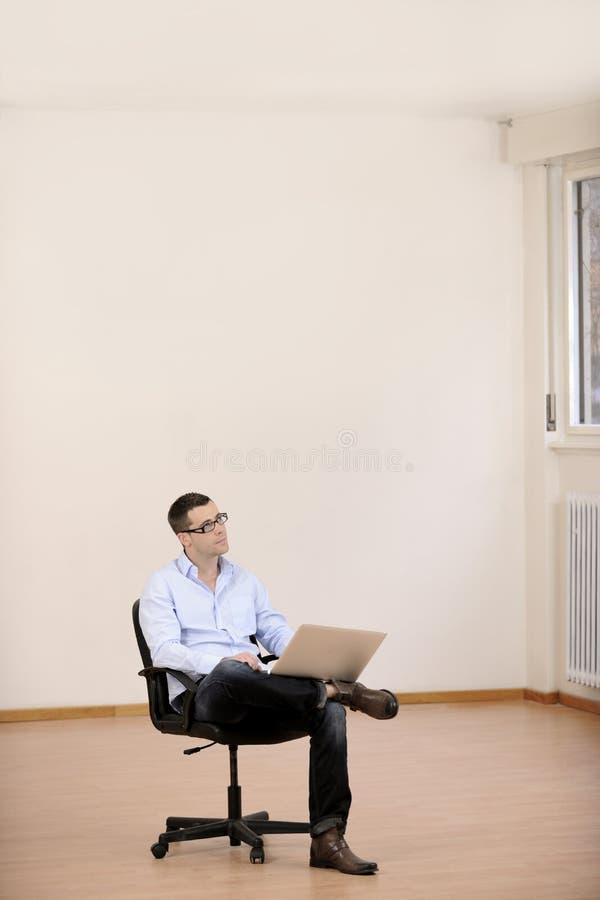 Geschäftsmann mit Laptop im neuen Büro stockfoto