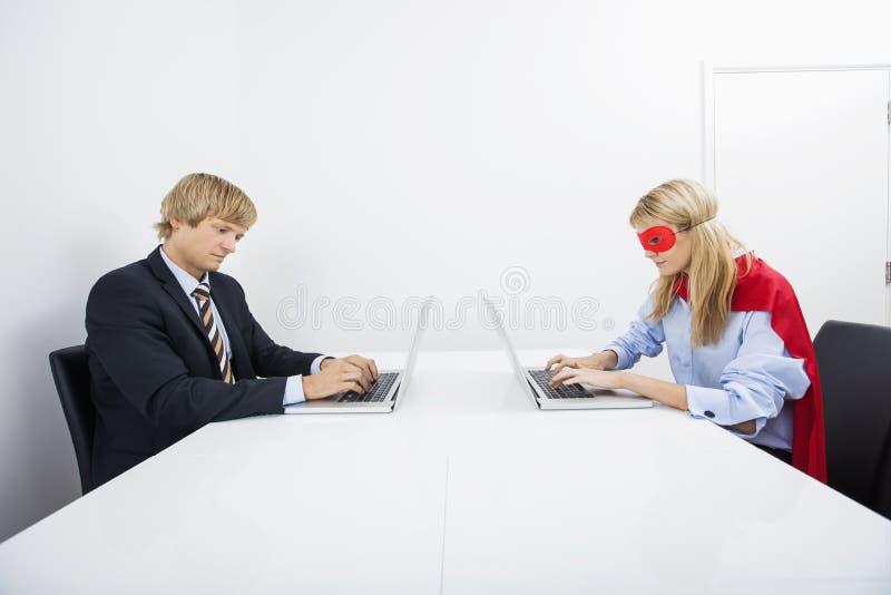 Geschäftsmann mit Mitarbeiter im Superheldkostüm unter Verwendung der Laptops im Büro lizenzfreie stockfotos