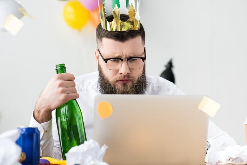 Geschäftsmann mit Papierkrone auf dem Kopf und Flasche Champagner in der Hand Laptopschirm betrachtend stockfotografie