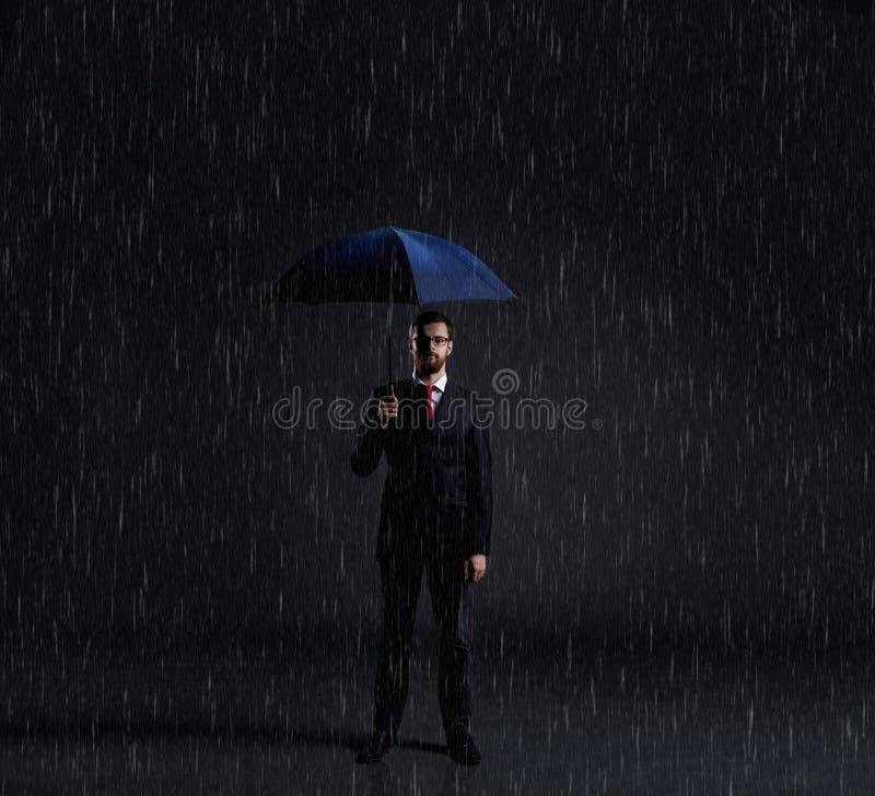 Geschäftsmann mit Regenschirm Schwarzer Hintergrund mit copyspace Busi lizenzfreie stockfotos