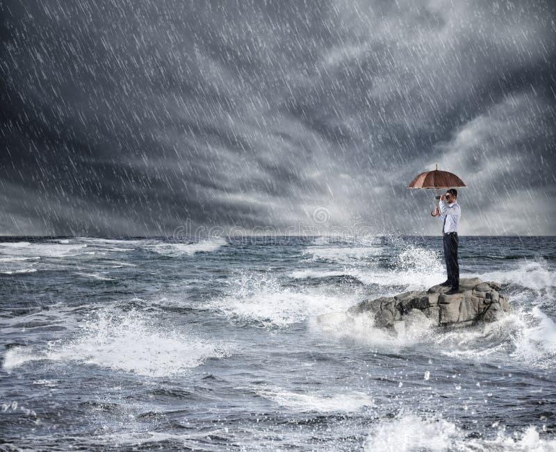 Geschäftsmann mit Regenschirm während des Sturms im Meer Konzept des Versicherungsschutzes stockbild