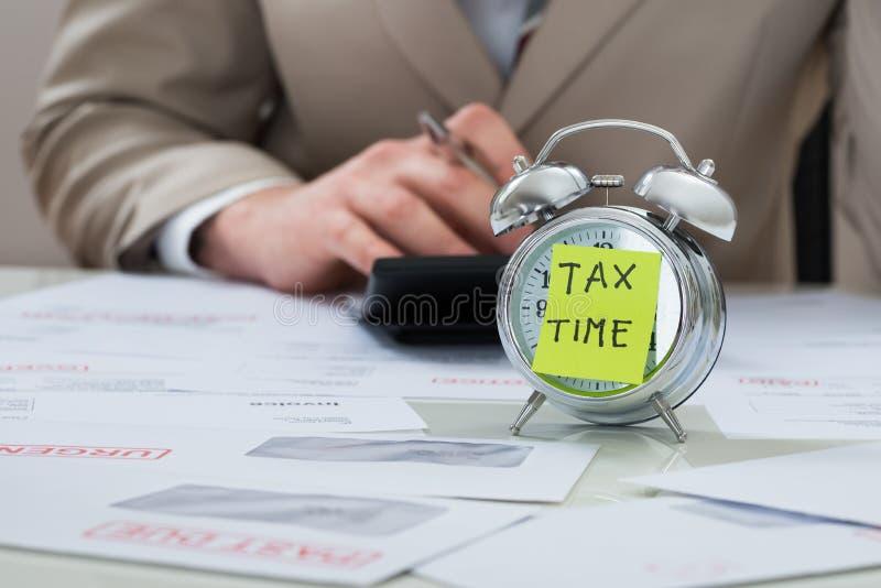 Geschäftsmann mit Steuerzeitanzeigenanmerkung über Wecker stockbild