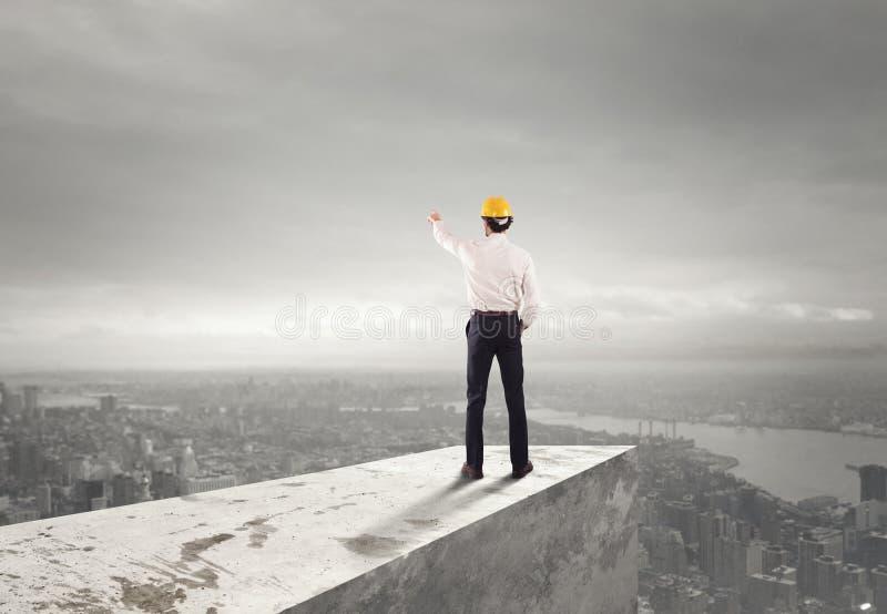 Geschäftsmann mit Sturzhelm zeigt die richtige Richtung an stockfoto