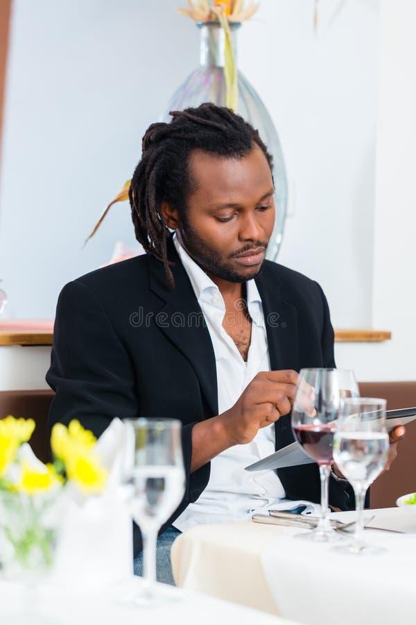 Geschäftsmann mit Tablette im Restaurant stockfotografie