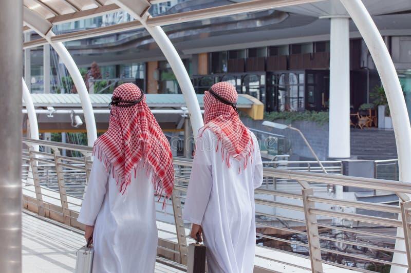 Geschäftsmann mit zwei Arabern mit Aktenkoffer und Weg zusammen herum stockbild