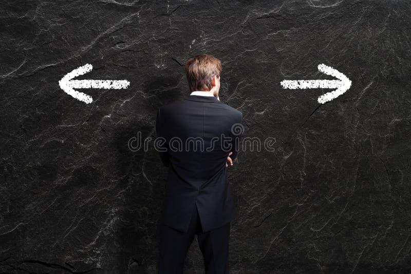 Geschäftsmann muss zwischen zwei Richtungen entscheiden lizenzfreies stockfoto