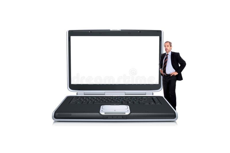 Geschäftsmann nah an einer Laptop-Computer lizenzfreie stockfotografie