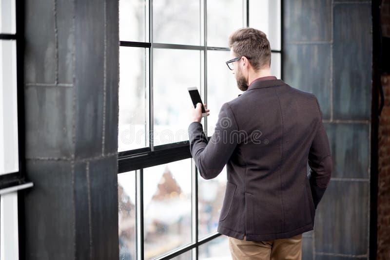 Geschäftsmann nahe dem Fenster stockbild