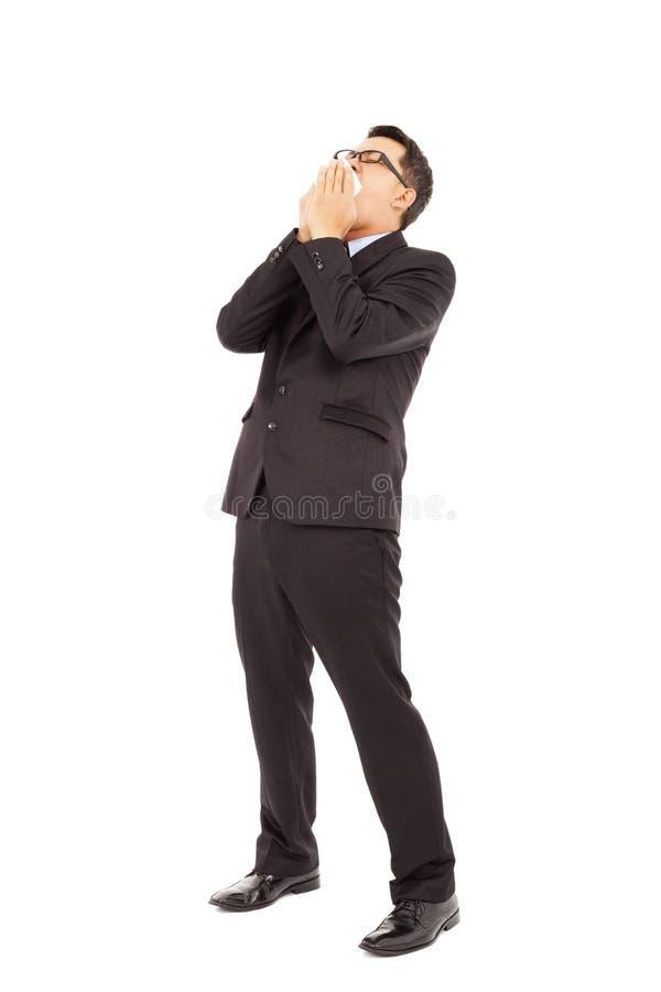 Geschäftsmann niest mit verbiegendem Körper stockbild