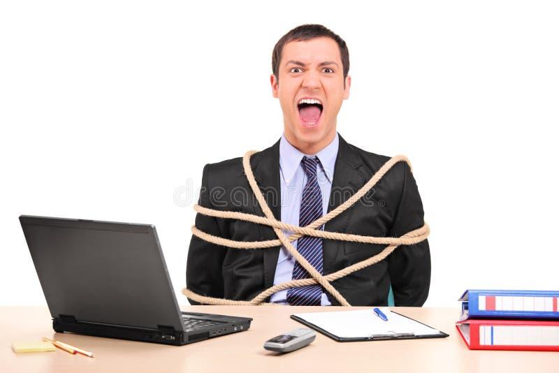 Geschäftsmann oben gebunden mit Seil im Büro lizenzfreie stockfotografie