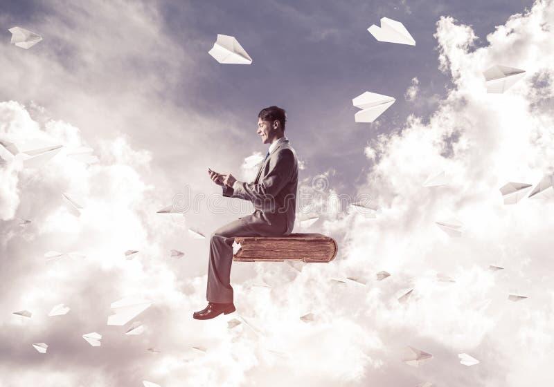 Geschäftsmann oder Student auf Buch und Papier planiert Fliegen herum stockfotografie