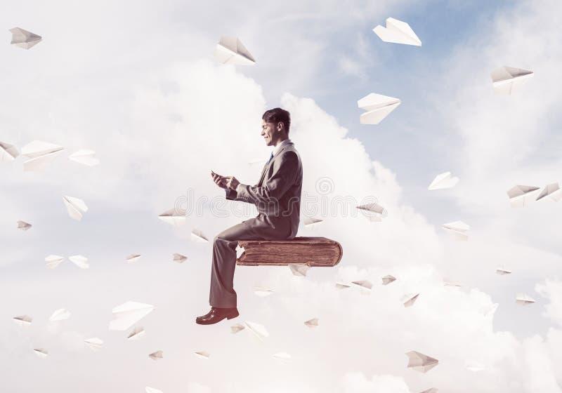 Geschäftsmann oder Student auf Buch und Papier planiert Fliegen herum stockbilder