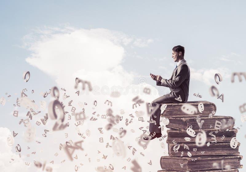 Geschäftsmann oder Student auf Buch und Symbole, die herum fliegen stockbilder