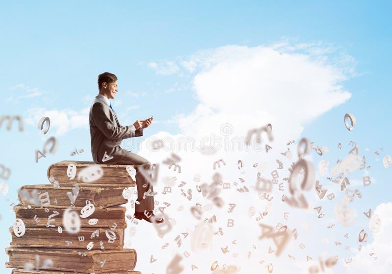 Geschäftsmann oder Student auf Buch und Symbole, die herum fliegen lizenzfreies stockfoto