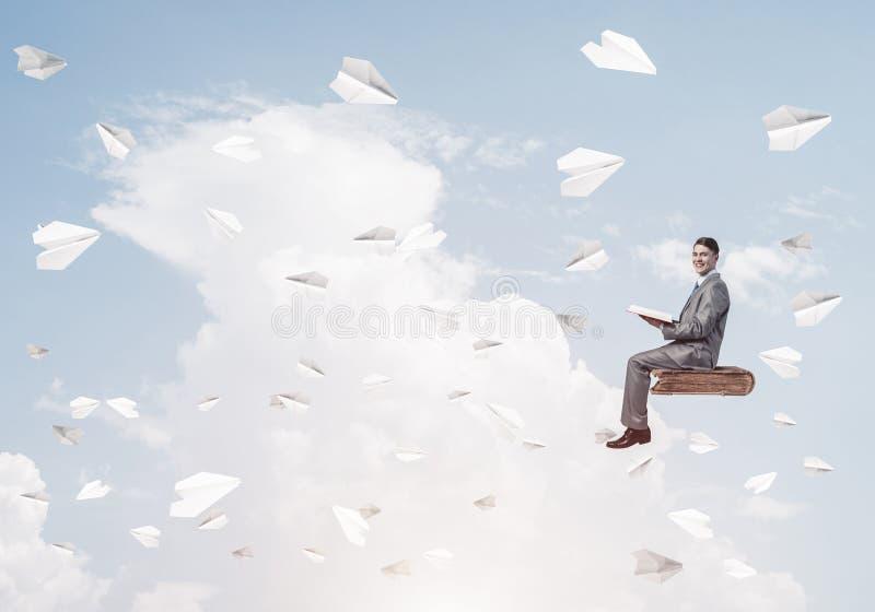Geschäftsmann- oder Studentenlesebuch- und -papierflugzeuge, die arou fliegen lizenzfreie stockfotos