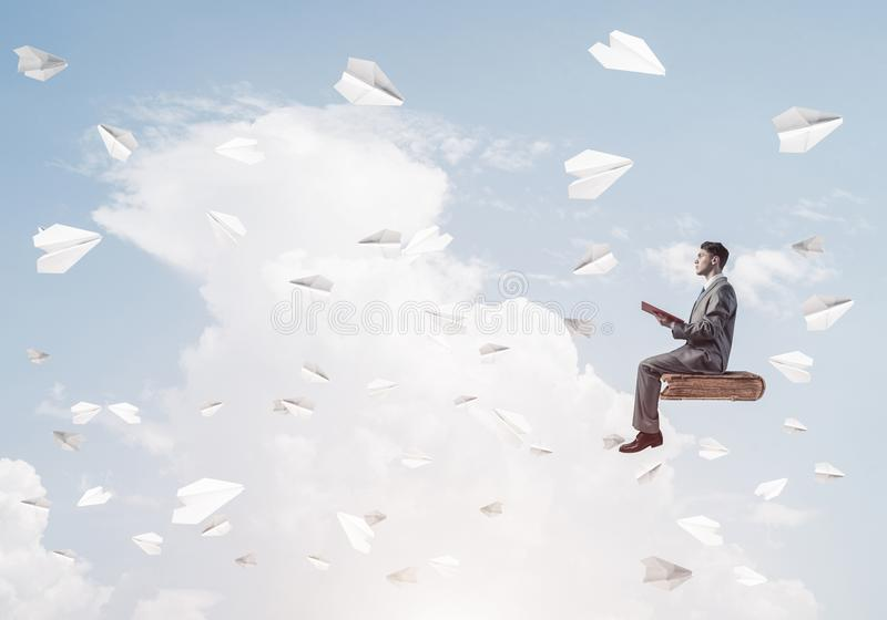 Geschäftsmann- oder Studentenlesebuch- und -papierflugzeuge, die arou fliegen stockbild
