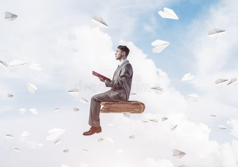 Geschäftsmann- oder Studentenlesebuch- und -papierflugzeuge, die arou fliegen lizenzfreies stockbild