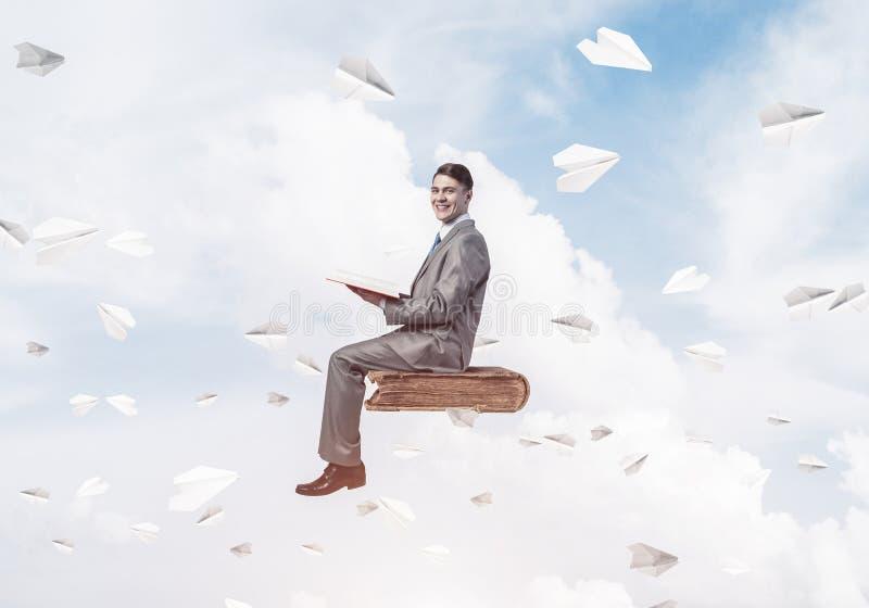 Geschäftsmann- oder Studentenlesebuch- und -papierflugzeuge, die arou fliegen lizenzfreie stockfotografie