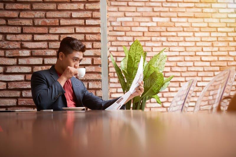 Geschäftsmann Reading Newspaper während des Frühstücks stockfotografie