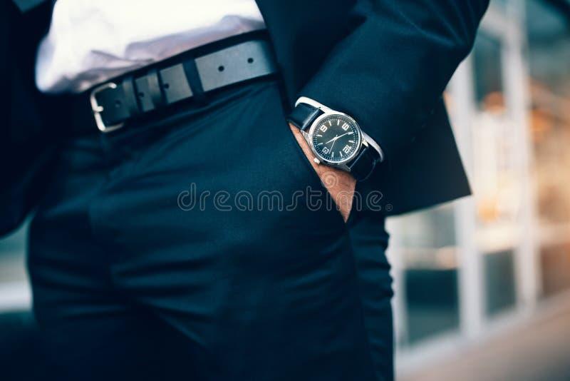 Geschäftsmann ` s Hand in der Tasche, die eine Uhr trägt lizenzfreies stockfoto