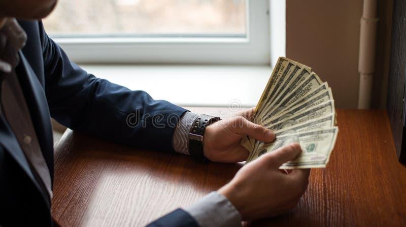 Geschäftsmann ` s Hand zum Halten des Geldes Handvoll Dollar auf hölzernem Hintergrund lizenzfreies stockfoto